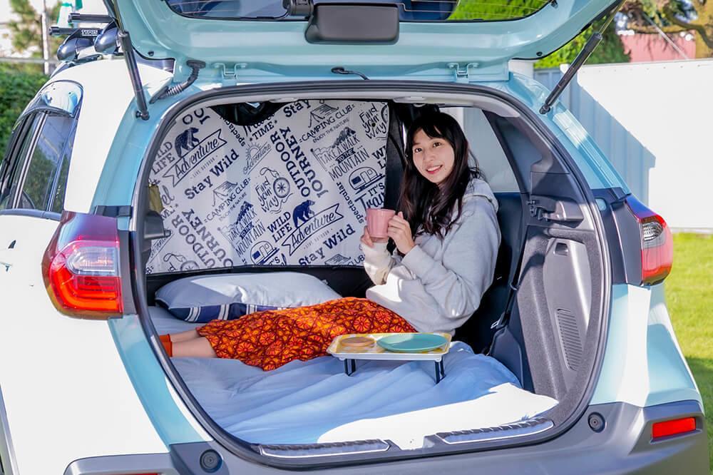 40_車中泊するために快適な空間にカスタムしたフィットクロスターの車内でくつろぐ森風美さん