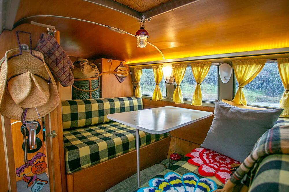 13 ワーゲンバスの車内には、テーブルと椅子がある。天井や壁は板張