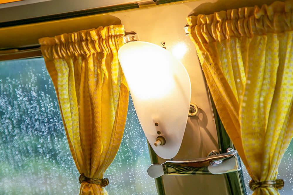 15 窓には黄色のカーテン、壁には貝殻のようなクラムシェルというライトが灯っている