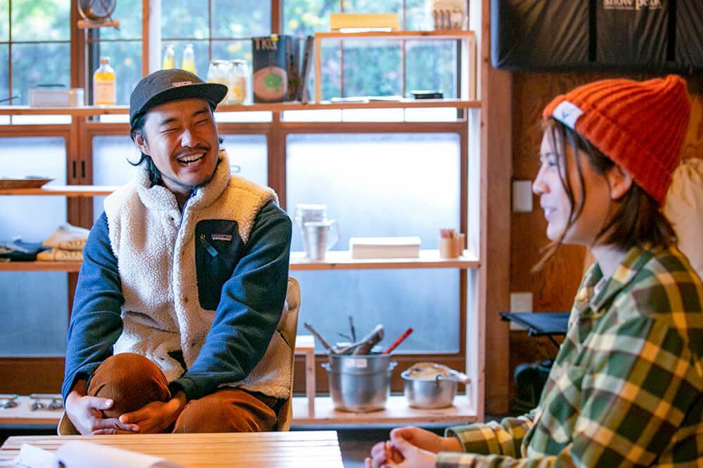 キャンプ民泊「NONIWA(ノニワ)」のリビングルームで笑顔で話をする野あそび夫婦