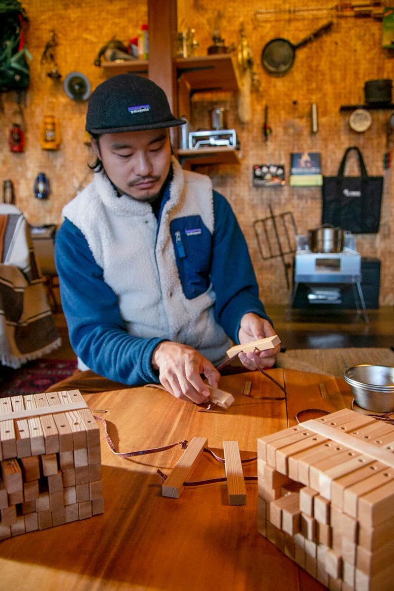 キャンプ民泊「NONIWA(ノニワ)」のリビングルームで木工製品の説明をする野あそび夫婦のアオさん