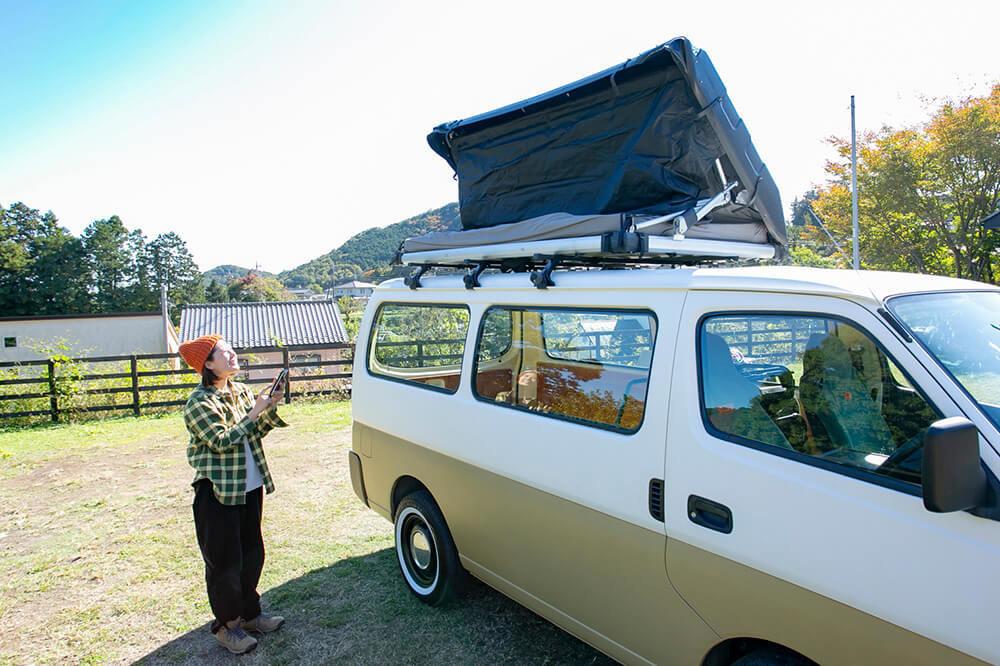 野あそび夫婦のバンライフ車、ルーフトップテントをスマホのアプリで開いているエリーさん