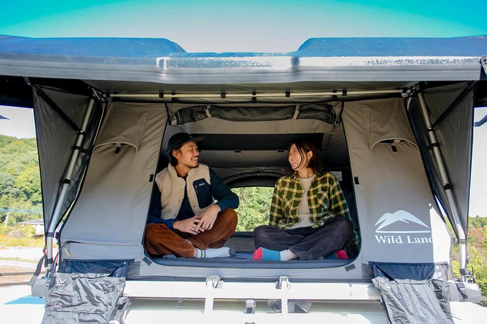 Wild Land(ワイルドランド)の「パスファインダー2」というルーフトップテントの内部で話をする野あそび夫婦