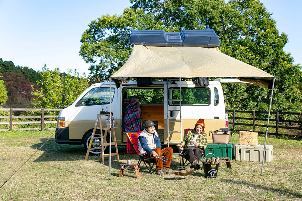 キャンプ民泊「NONIWA(ノニワ)」で、カーサイドタープの下でくつろぐ野あそび夫婦