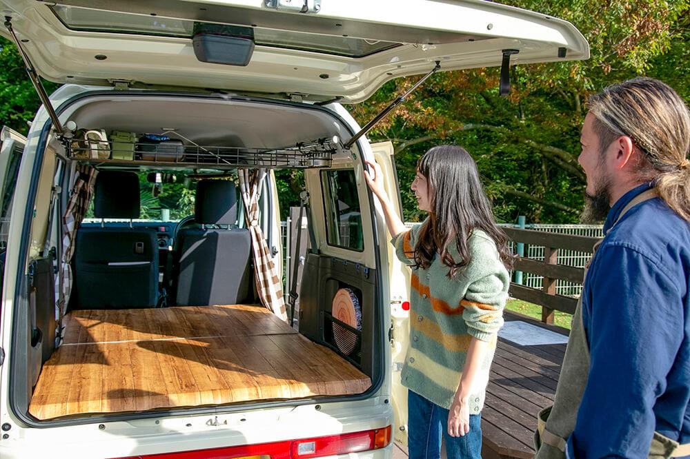 ホンダの軽自動車「バモスホビオ」の中を見ている女子キャンパーの森風美さんとバンライファーの鈴木大地さん