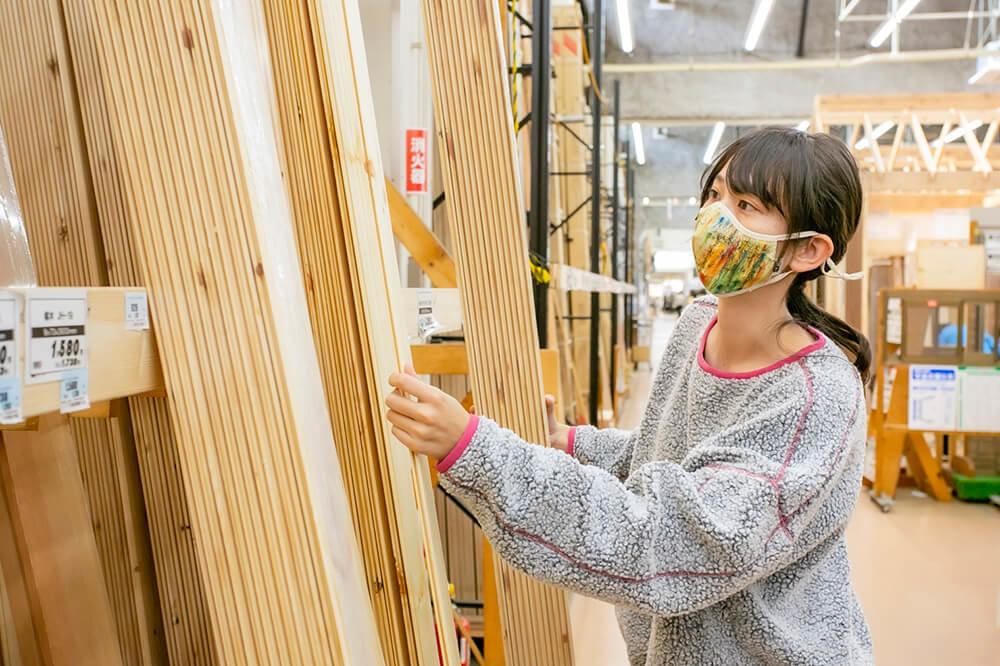 ホームセンター「ジョイフル本田 ニューポートひたちなか店」で、車内の天井を板張りにするための板を選ぶ女子キャンパーの森風美さん