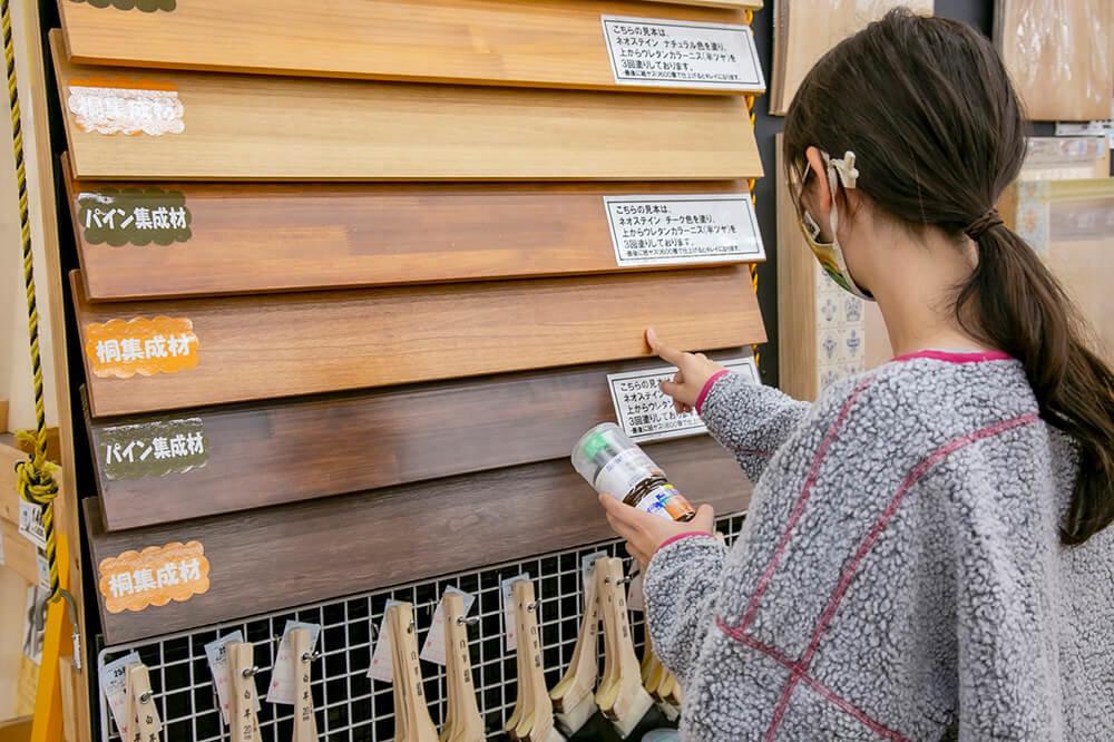 板に塗るオイルを選ぶ女子キャンパーの森風美さん