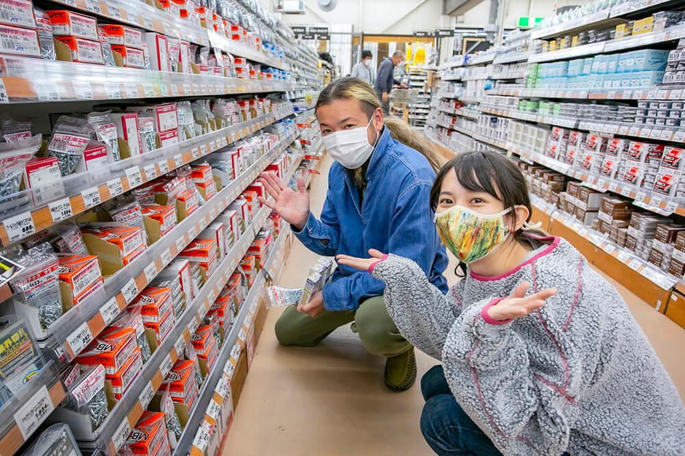 ホームセンター「ジョイフル本田 ニューポートひたちなか店」の釘・ネジ売り場にて。種類が豊富で何を選んだらいいか迷っている森風美さんと、アドバイスする鈴木大地さん