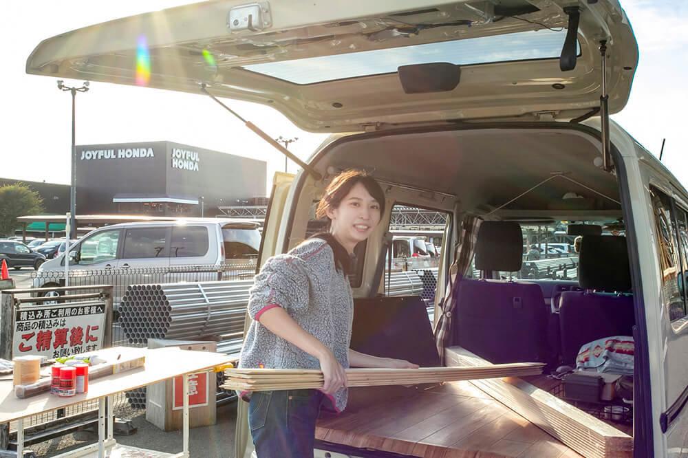 ジョイフル本田の駐車場に停めたバモスホビオに、購入した木材を積み込む森風美さん