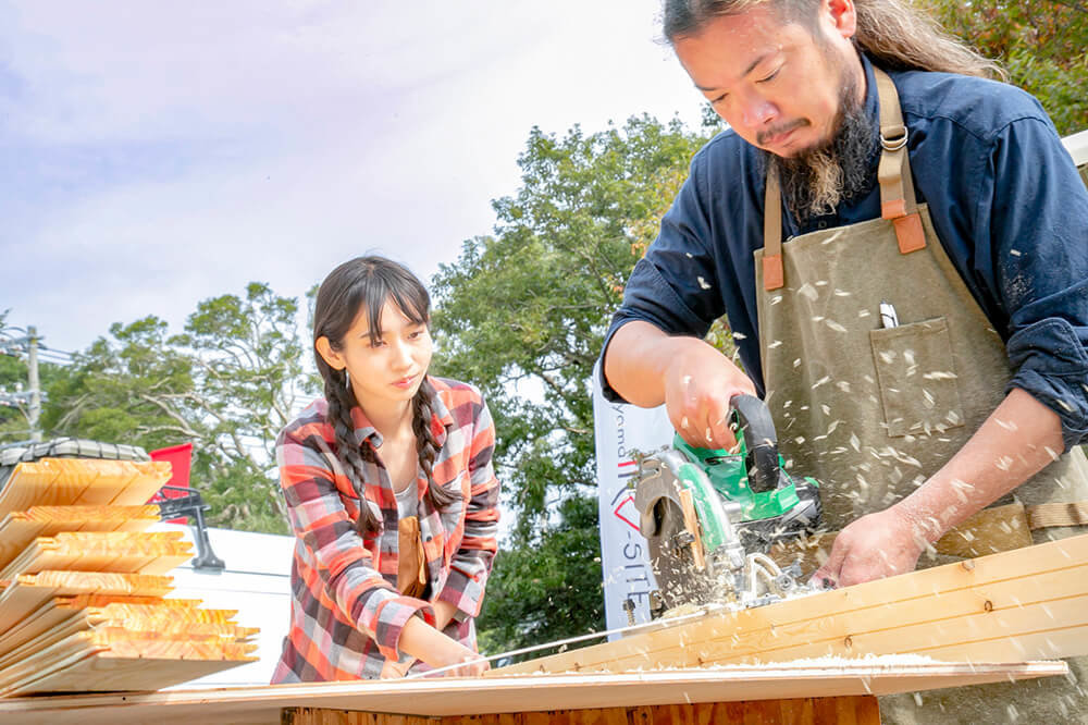 天井に張る板を電動丸ノコで削っている鈴木大地さんと、板を押さえる森風美さん