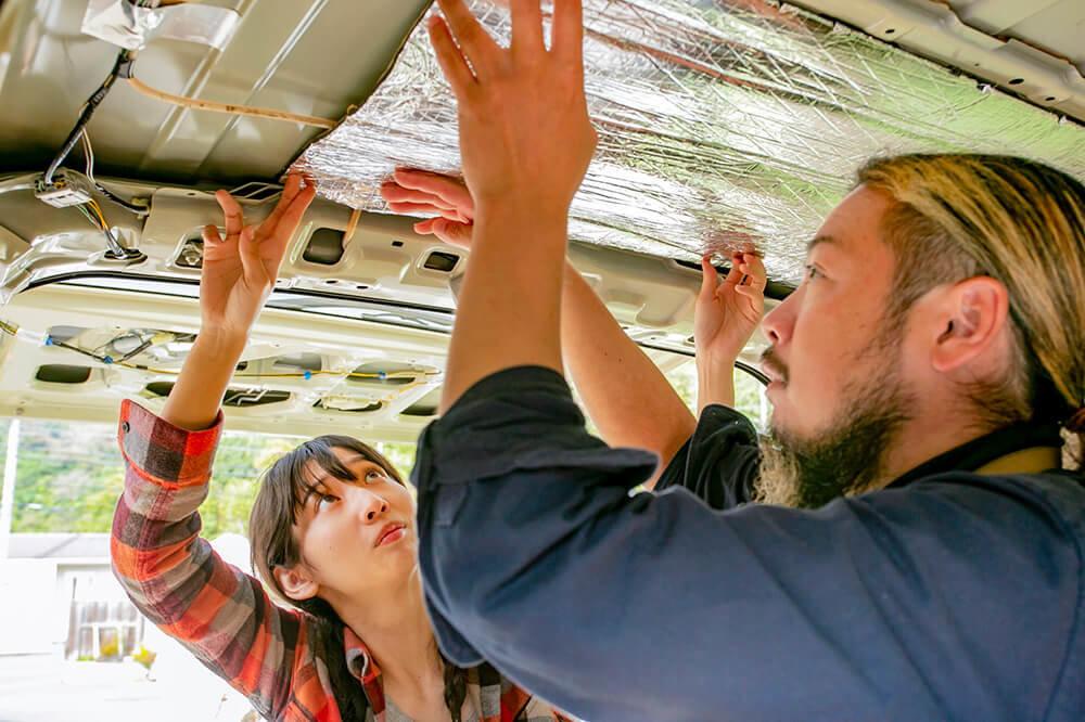 カットした断熱材を車の天井に貼っている森さんと鈴木さん