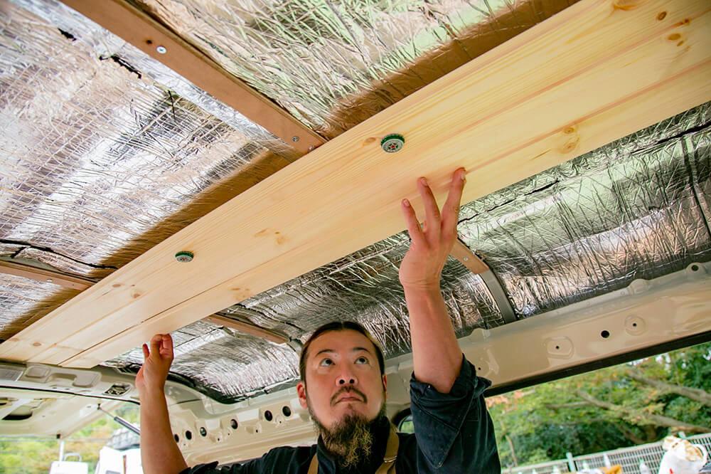 天井の板を貼っている鈴木さん