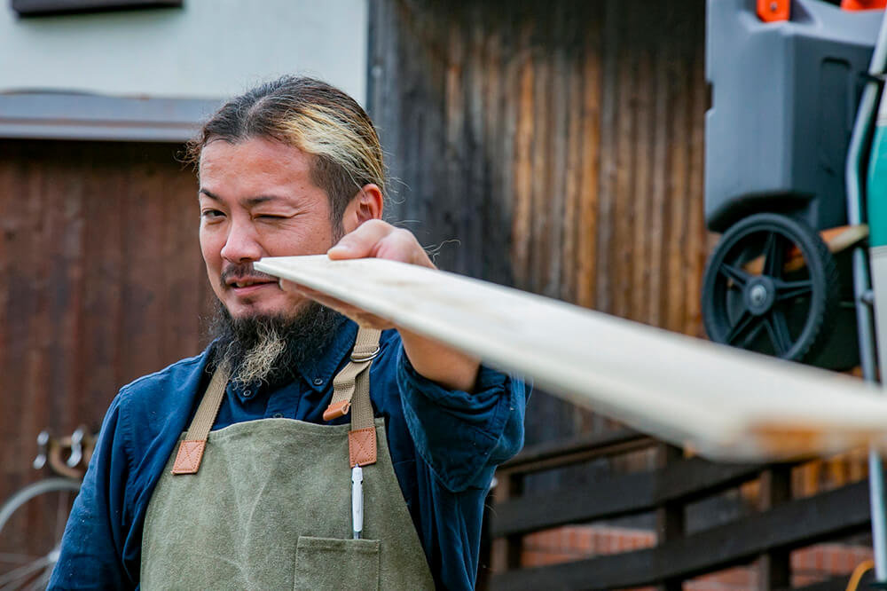 緩やかなカーブをつけた板を、片目をつぶって見ている鈴木さん
