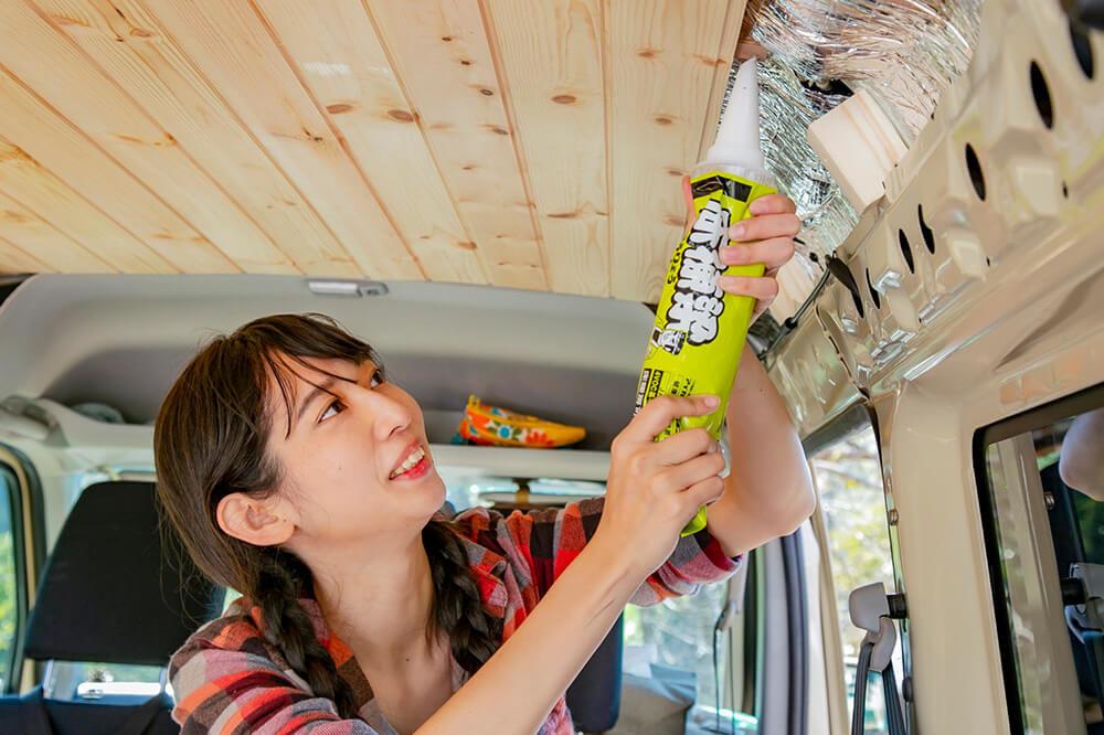 天井の下地材に接着剤を塗っている森風美さん