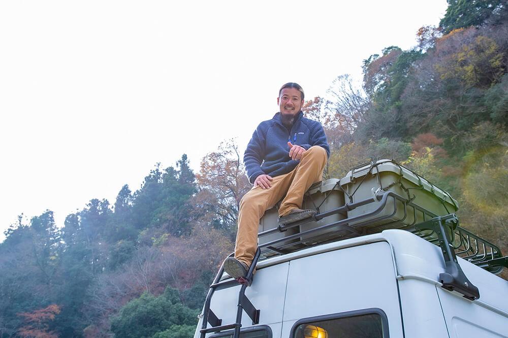 ルーフキャリアの上に積んだコンテナの上に座る鈴木さん