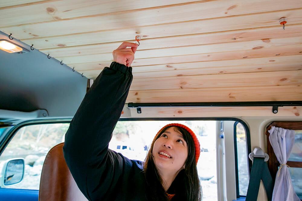 森風美さんが天井板にマグネットフックをつけているところ