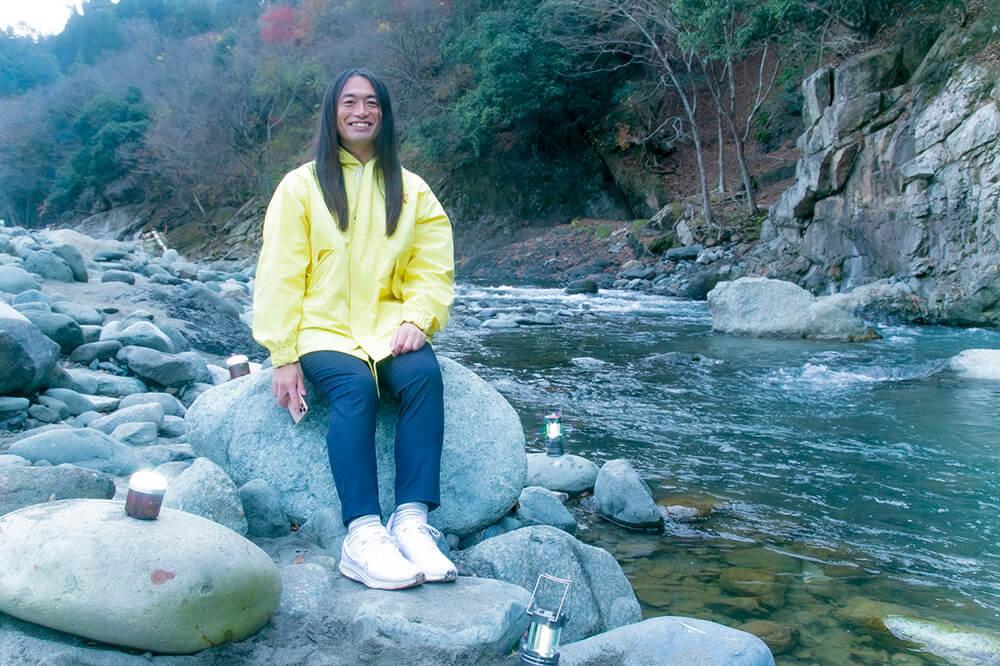 占い師のLove Me Doさん(ラブちゃん)がキャンプ場の河原の石の上に座っている