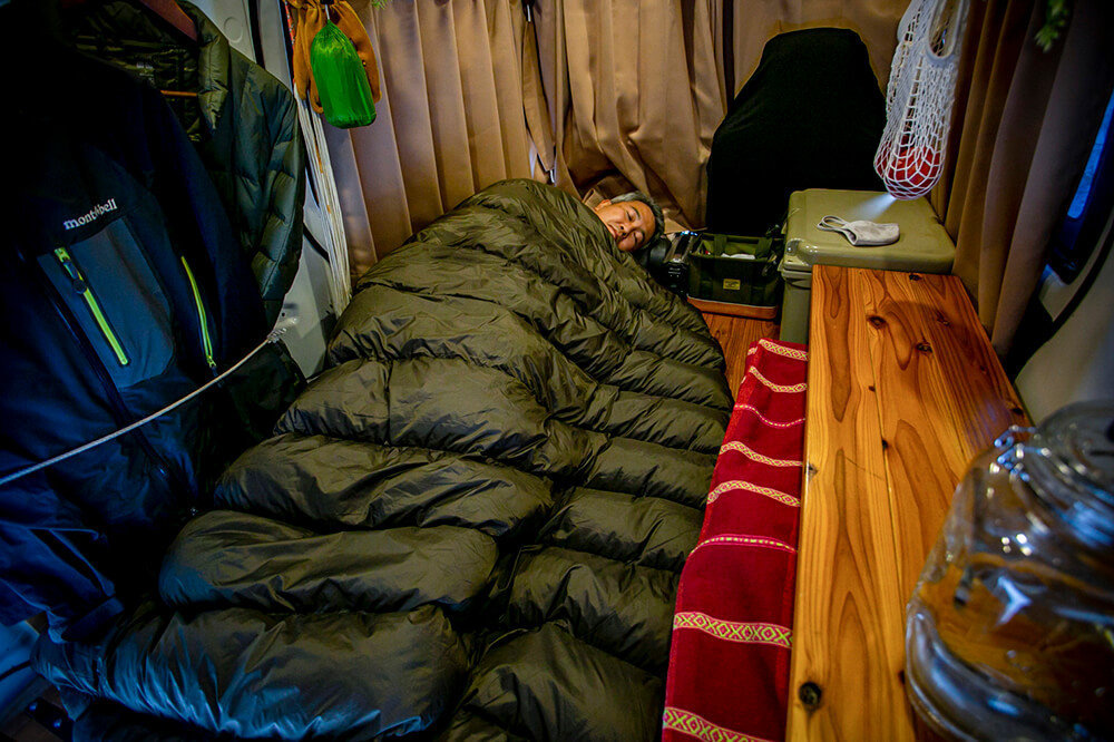 車内のカーテンを閉め、ハイランダーの封筒型ダウンシュラフに入り、渡辺さんが寝ているところ