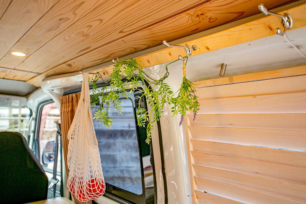 壁の天井に近いところに板を貼ってフックをつけている。フックには、リンゴが入ったネットバッグを吊るしたり、フェイクグリーンを飾ったりしている