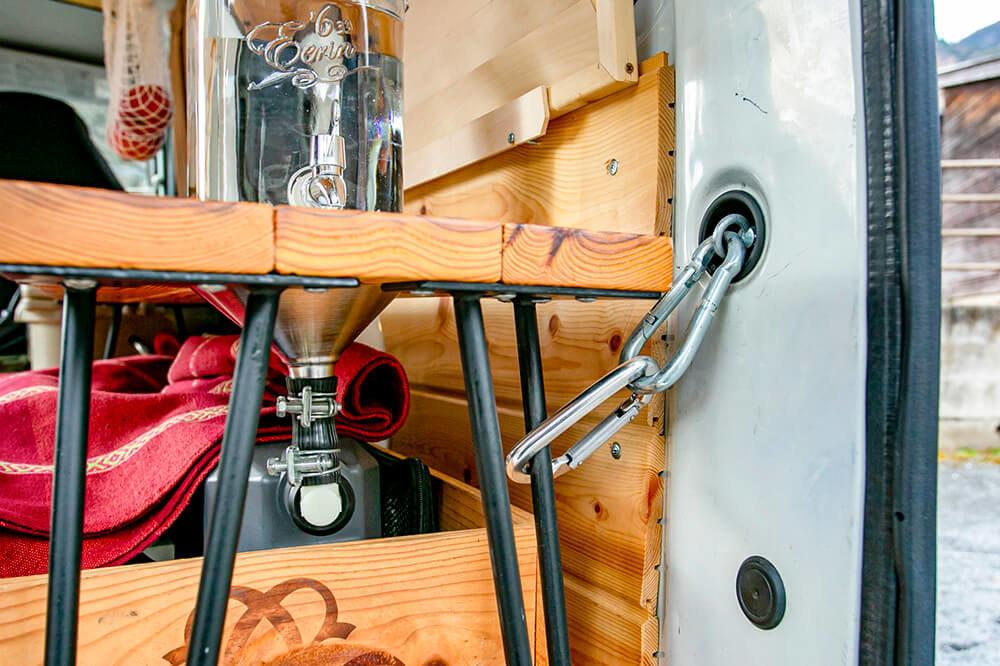 荷掛け用の穴(ユースフルホール)にカラビナでサイドテーブルの脚を固定している