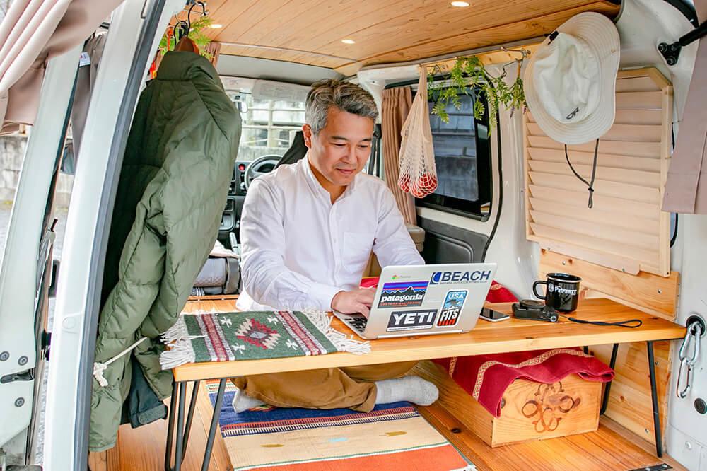 サイドテーブルをリア側に横置きして、外を眺めながら仕事をする渡辺圭史さん