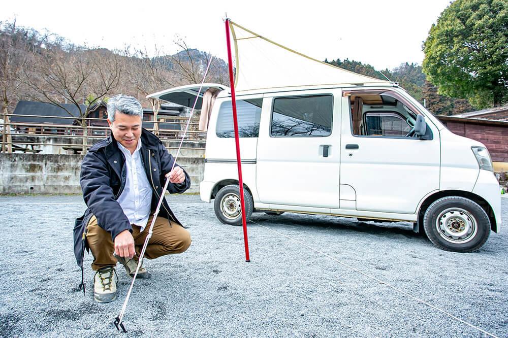 カーサイドタープを設置している渡辺さん