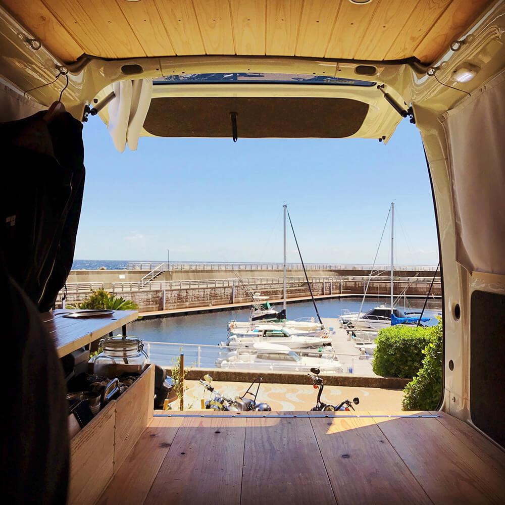 静岡県伊東市の道の駅「伊東マリンタウン」にて。バックドアを開けて、外には海とボートが見える