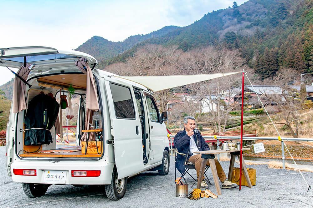ケニーズ・ファミリー・ビレッジ/オートキャンプ場で、カーサイドタープの下でコーヒーを飲む渡辺さん