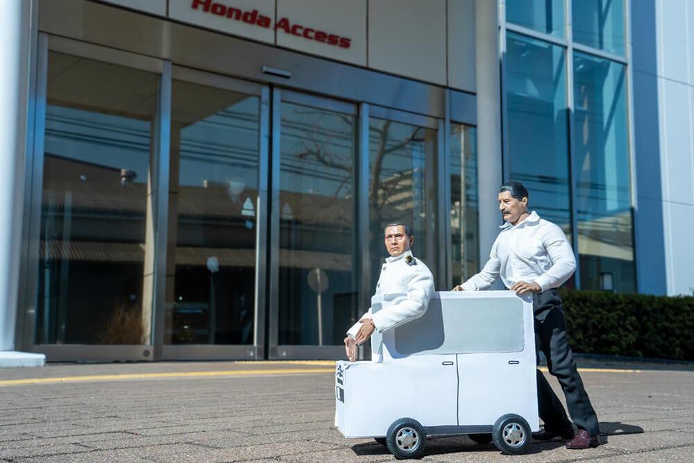 ミフネカーに乗ってミフネさんとヨシダさんがホンダアクセス本社の正面玄関に到着したところ