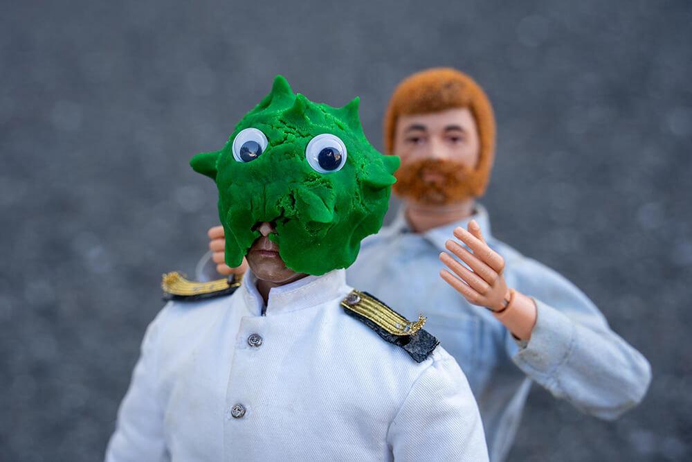 緑色のウイルスに扮するためのマスクを頭にかぶっているミフネさん