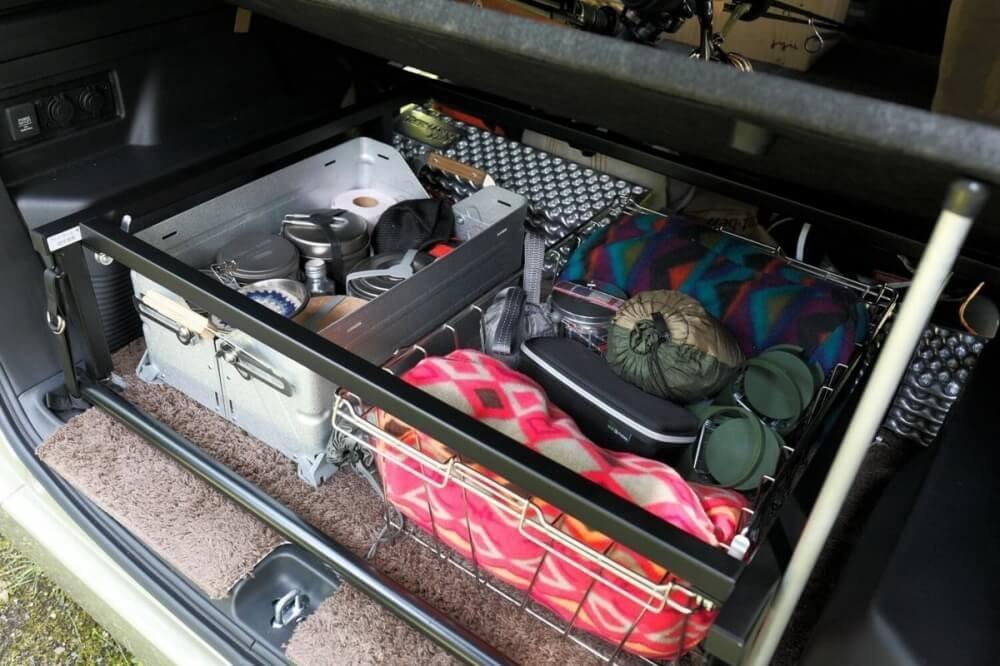 車中泊ベッドの下の収納スペースに食器やブランケットが入っている