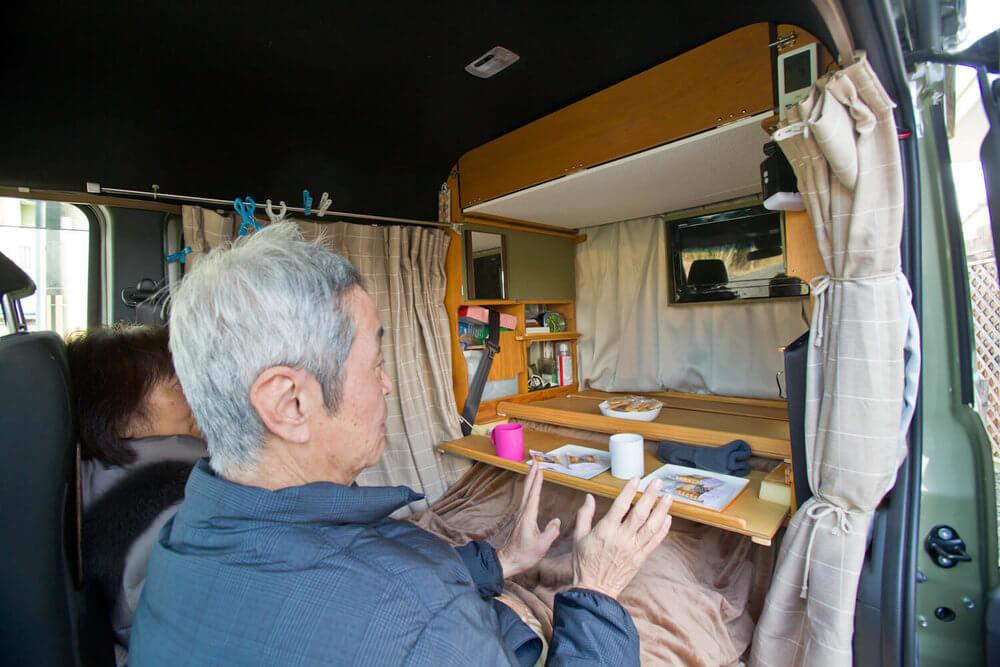 N-VANにDIYカスタムで取り付けたコタツに入り、テレビを見る岩見さん