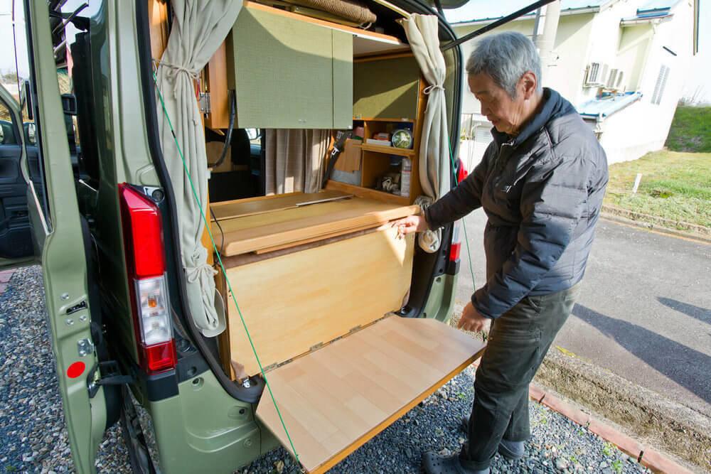 N-VANをカスタムして取り付けた仕切り板を倒すとテーブルになる仕組みを説明する岩見さん