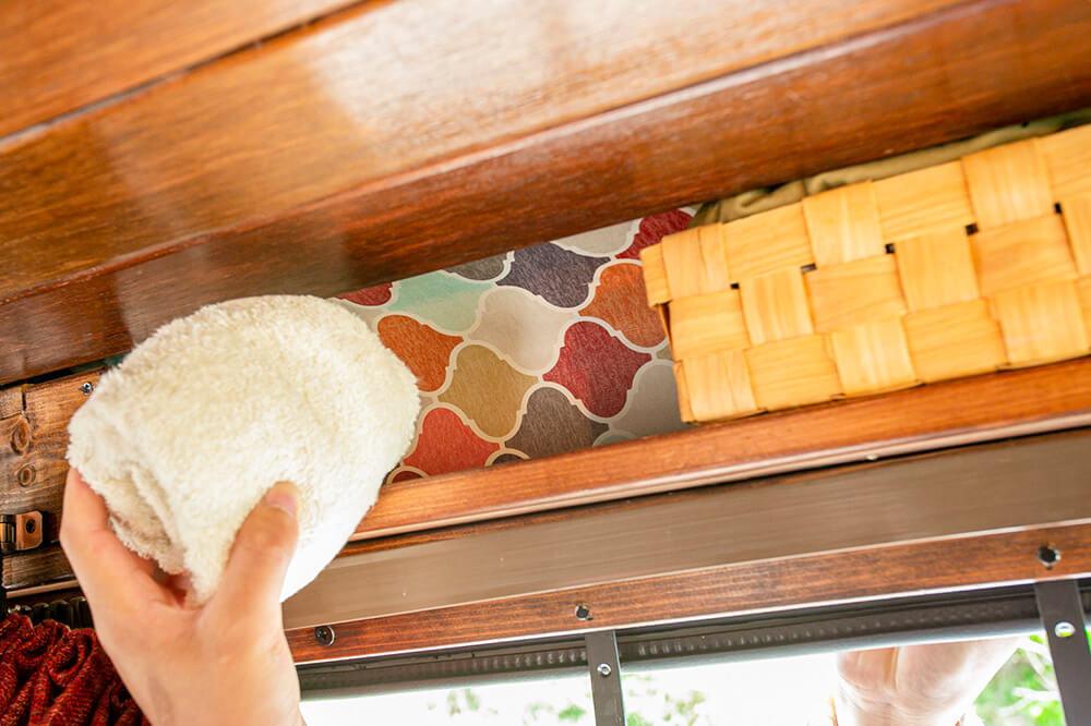 車内の自作の棚からタオルを取り出すところ