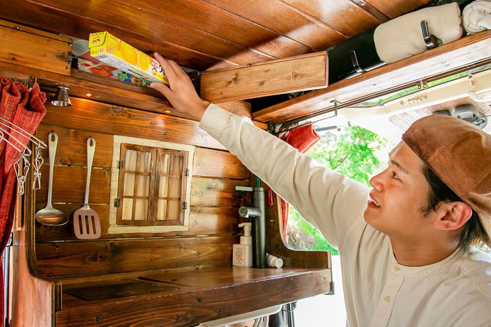 キッチン上部の戸棚からラップを取り出すはやとさん