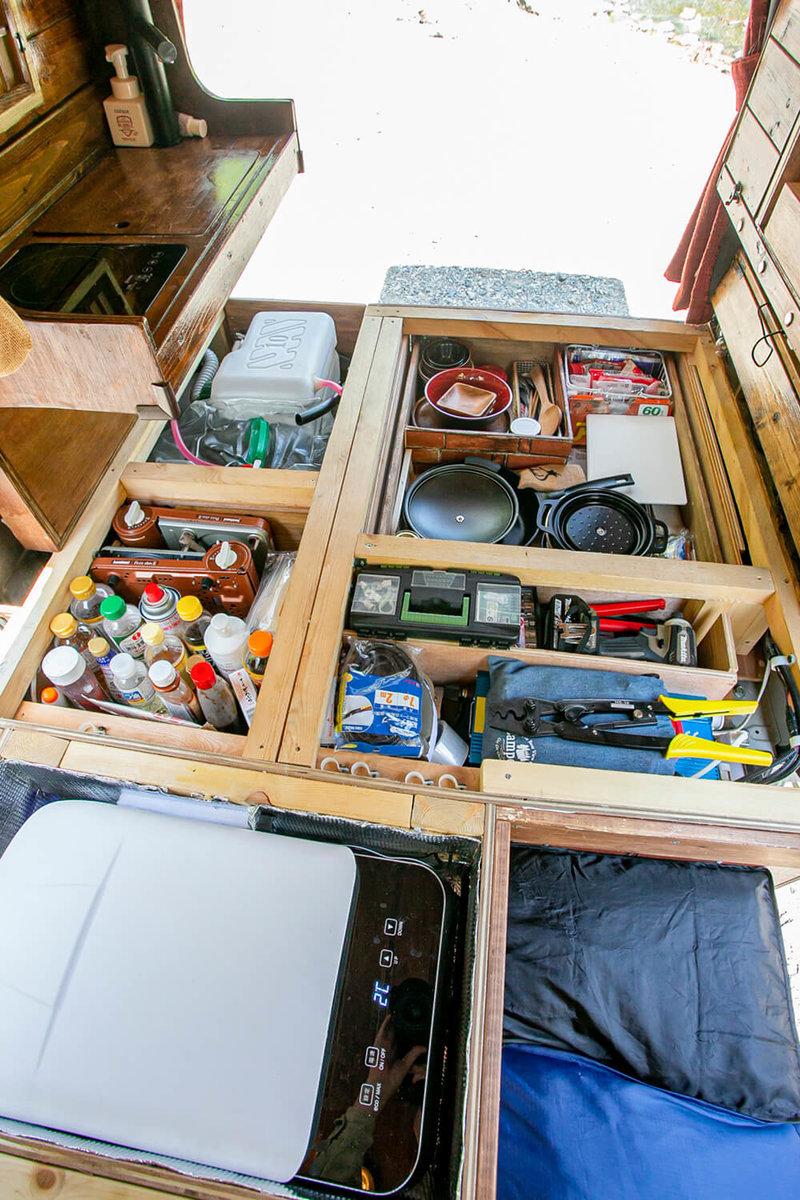 車内の床の収納スペースに調味料や食器、冷蔵庫、工具などが入っている