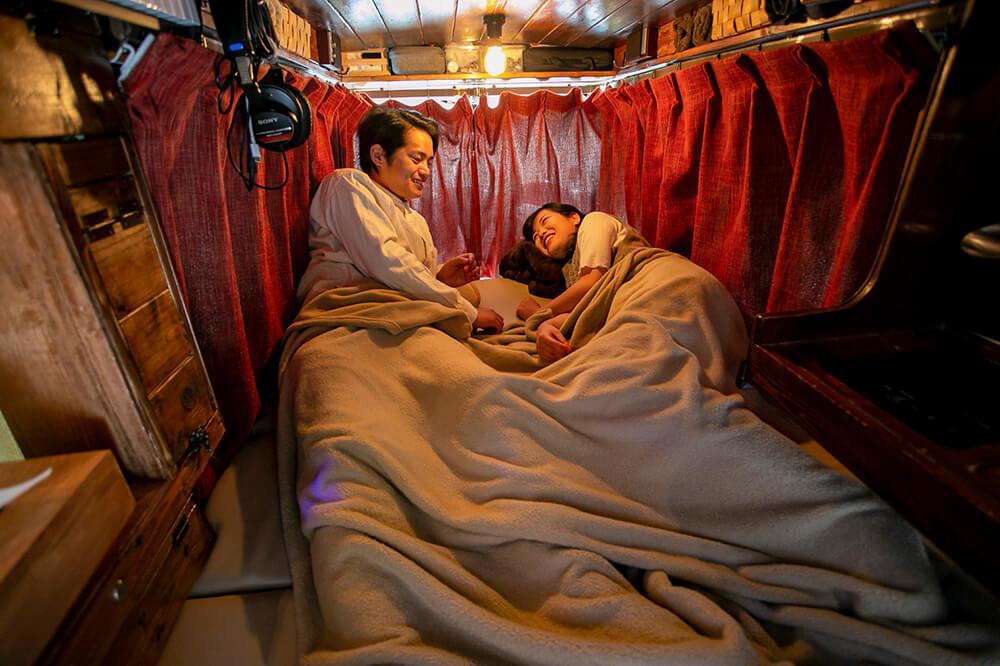 カーテンを閉めて、ふとんを敷き、夜、寝るときの様子を再現するあかねさんとはやとさん