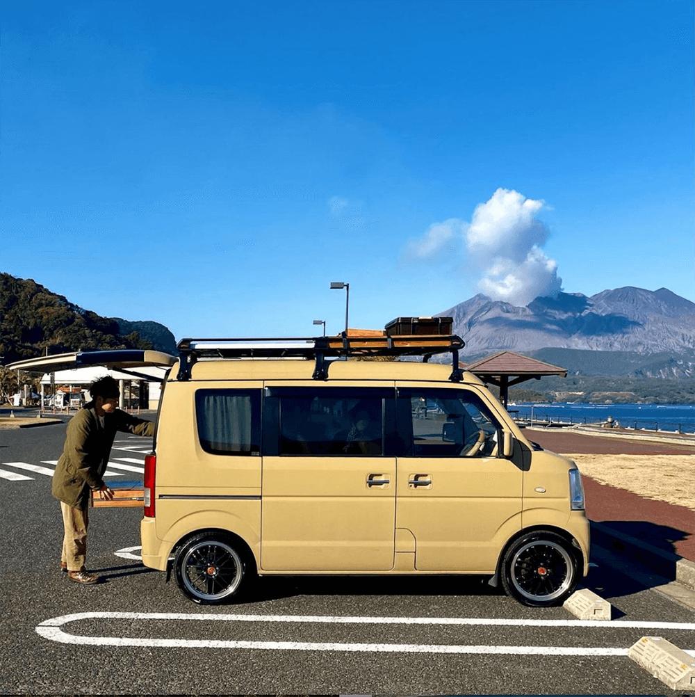 鹿児島県の駐車場に車を停めて、車の後ろでテーブルを出しているはやとさん。背後に桜島が見える。