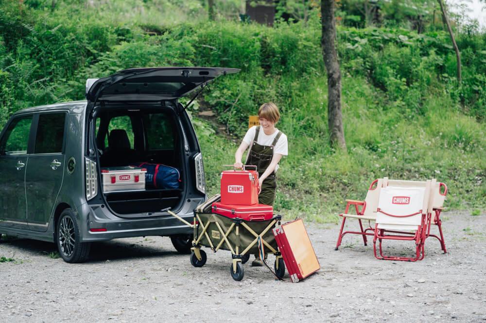 Honda N-WGNの荷室からCHUMSのキャンプギアを降ろす佐藤さん