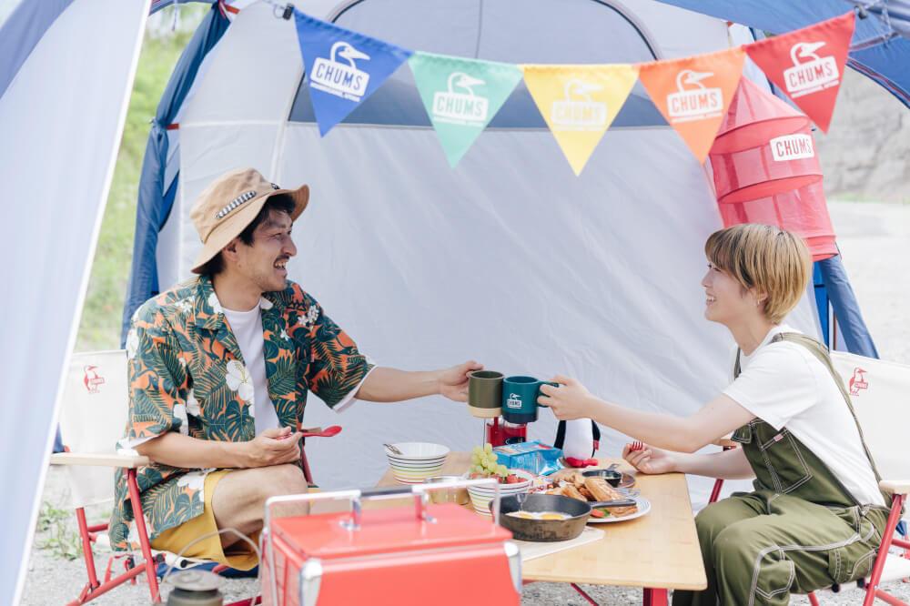 CHUMSのアイテムやギアに囲まれ、テントで乾杯する市之瀬さん、佐藤さん