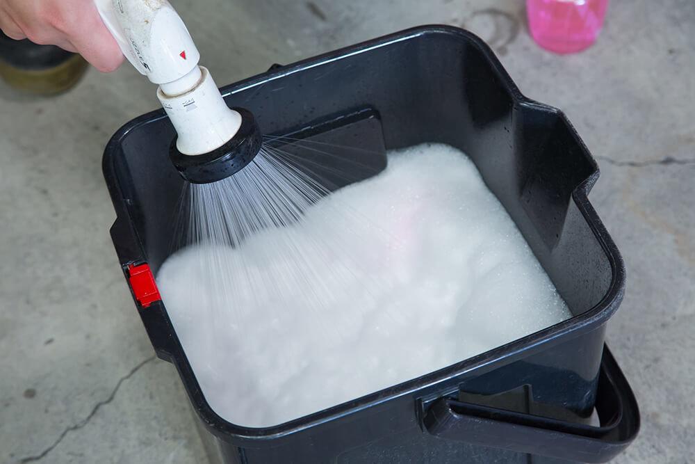 バケツの洗剤を泡立てる洗車ソムリエ・高橋宏宗さん