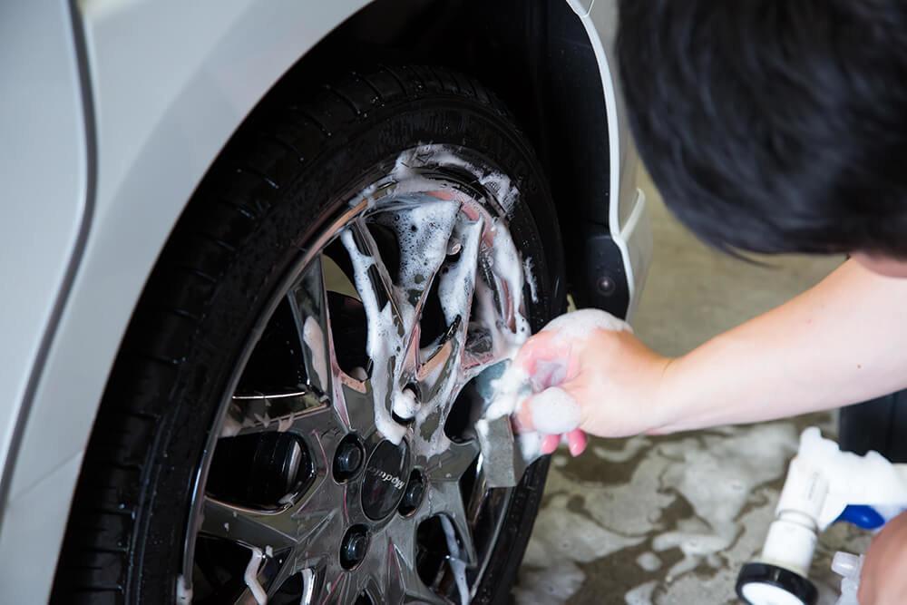 N-BOXのタイヤを洗う洗車ソムリエ・高橋宏宗さん