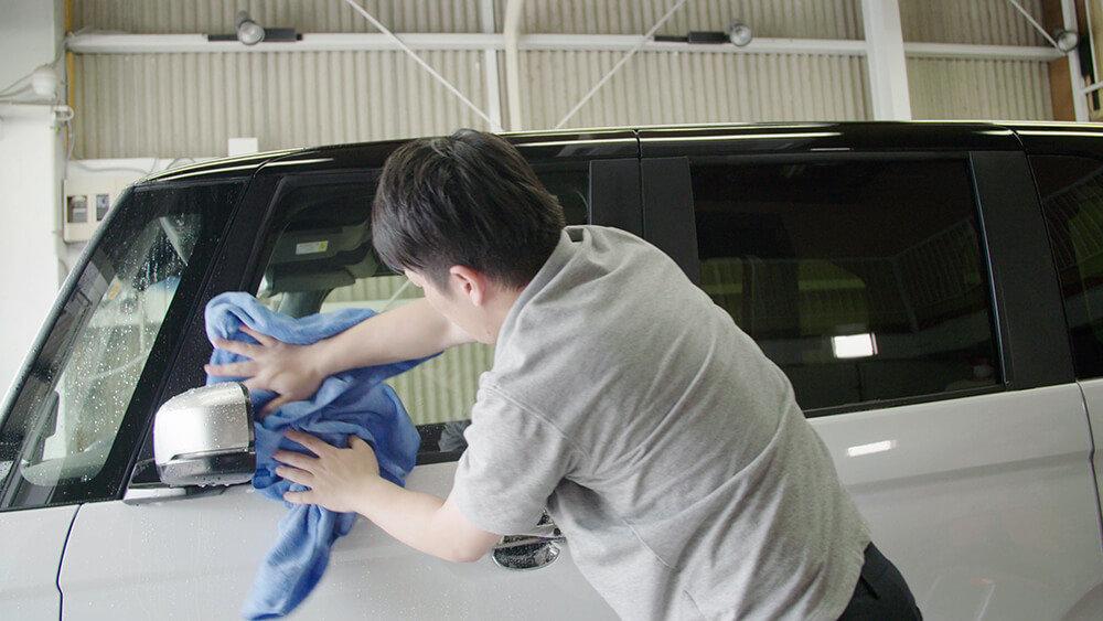 N-BOXのボディを拭く洗車ソムリエ・高橋宏宗さん