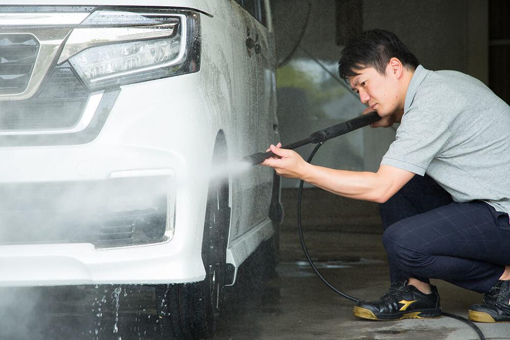 N-BOXのタイヤ周りを高圧洗浄機で洗う洗車ソムリエ・高橋宏宗さん
