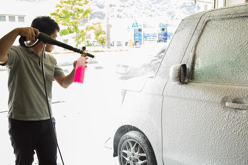N-BOXのボディに高圧洗浄機で洗剤を吹きかける洗車ソムリエ・高橋宏宗さん