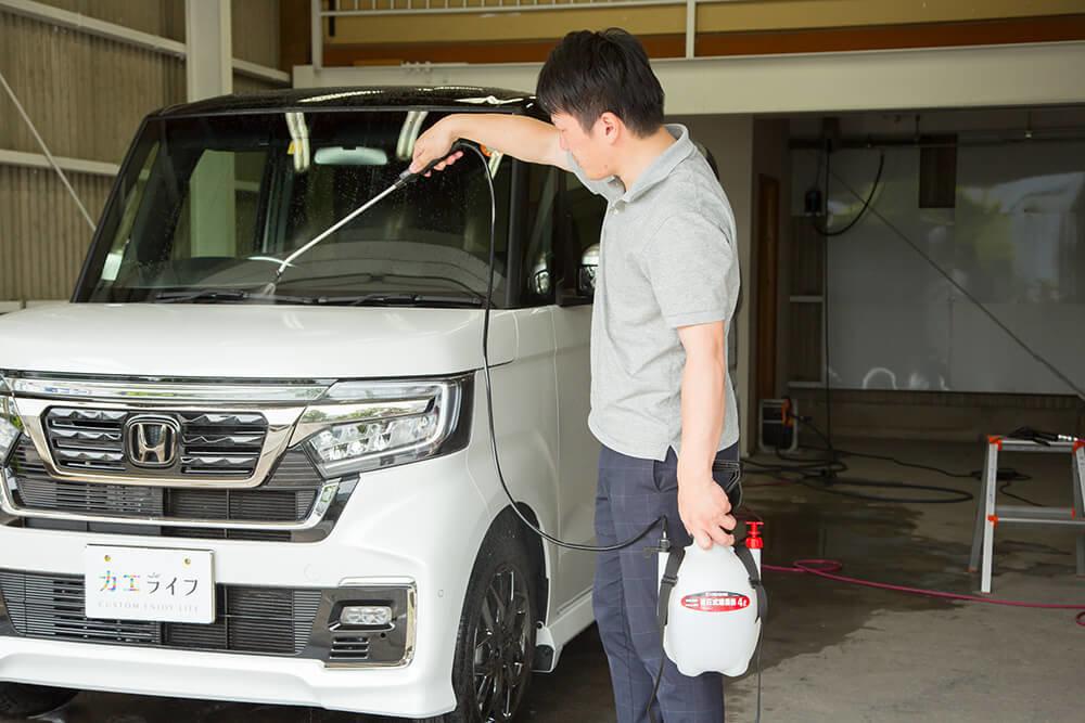 N-BOXのボディに鉄粉除去剤をスプレーする洗車ソムリエ・高橋宏宗さん