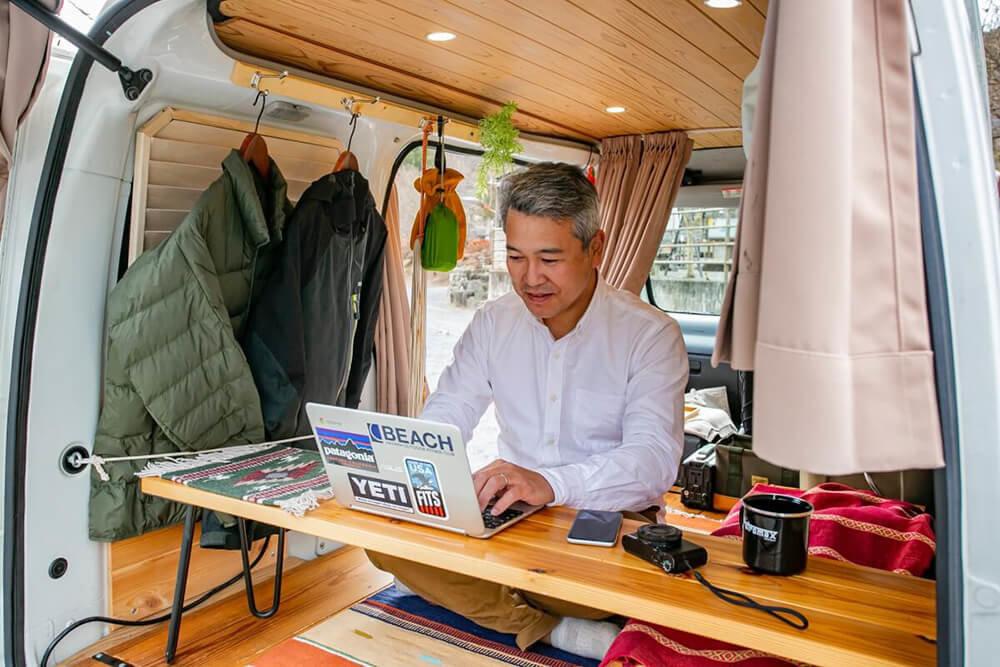軽バンを改造したキャンピングカーの車内で車中泊場所を探す渡辺圭史さん