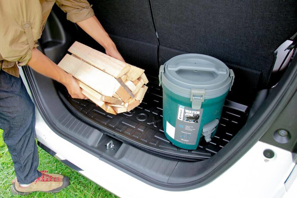 Hondaの軽自動車N-BOXの純正アクセサリー「ラゲッジトレイ」の上に、ウォータージャグと薪を置いた様子