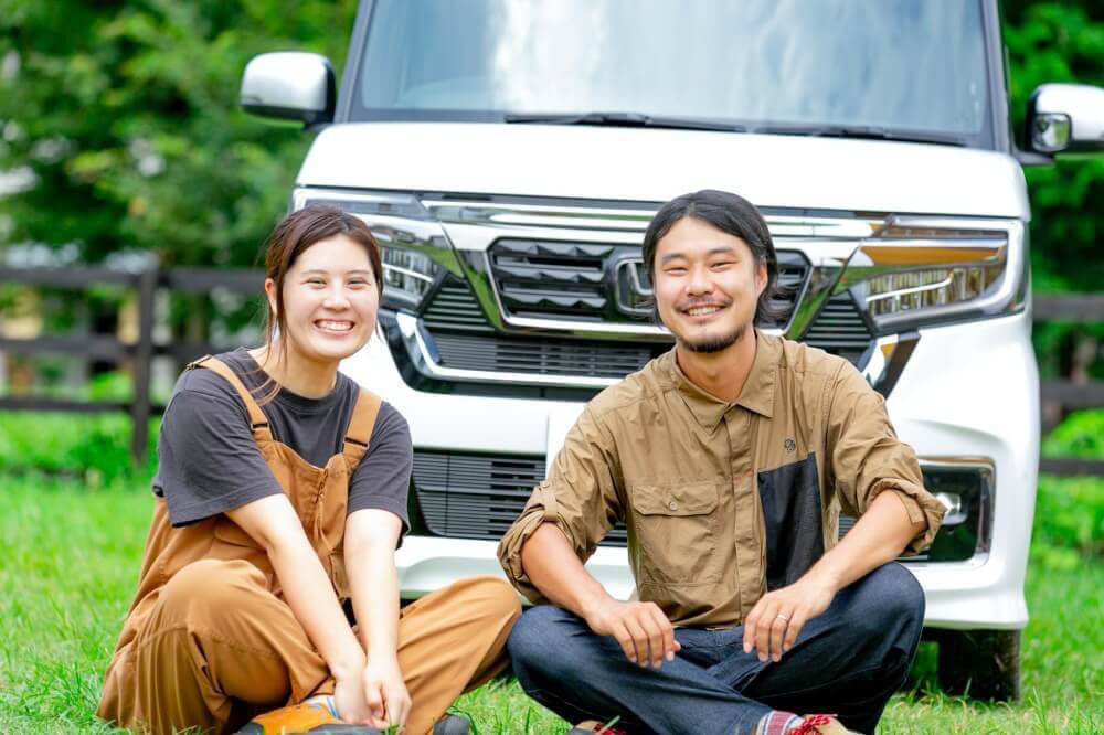 Hondaの軽自動車N-BOXの前で座る野あそび夫婦