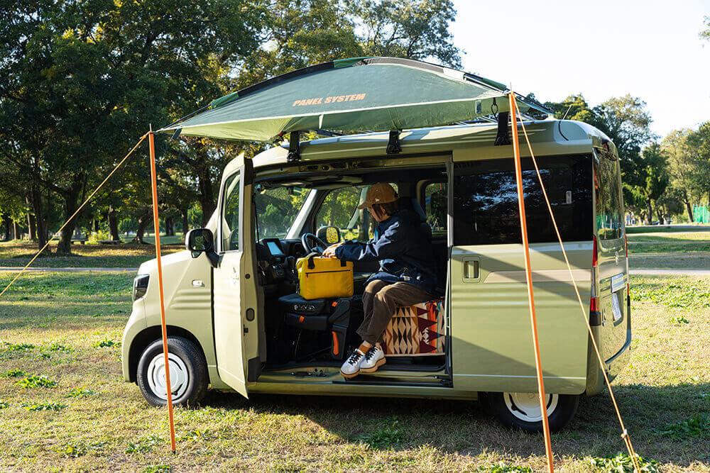 Hondaの軽自動車N-VANに、ロゴスのパネルLINK タープ200(後継モデル:neos Link Panel・PLR)を取り付け。こいしさんが車内に腰掛けている使用イメージ
